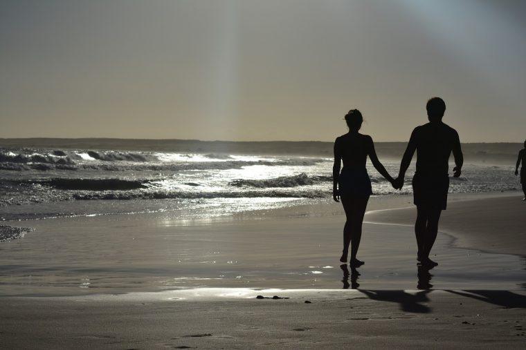 浜辺で手を繋いで歩くカップル