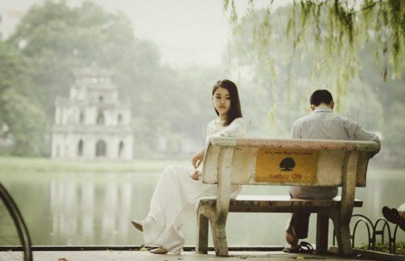 ベンチで考え事をするカップル