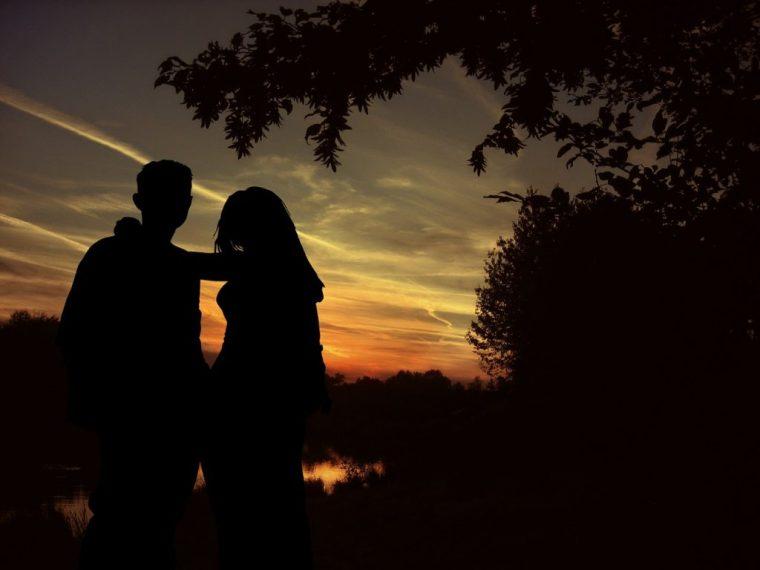 夕焼けを背景にするカップル