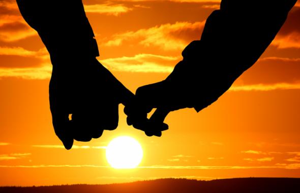 夕日の前で指を繋ぐカップル