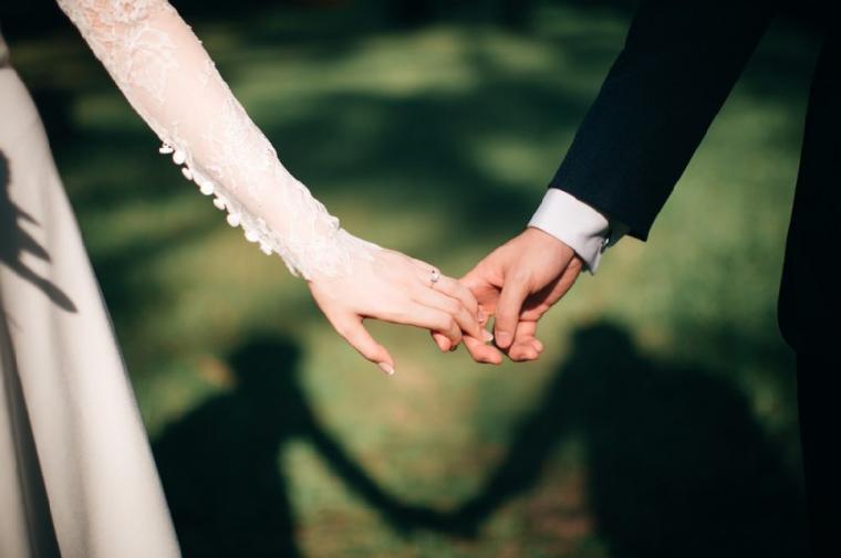 手を繋ぐ結婚式中の夫婦