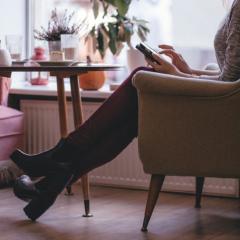 椅子で携帯を操作する女性