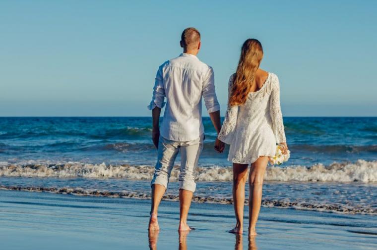 浜辺で手を繋ぐカップル
