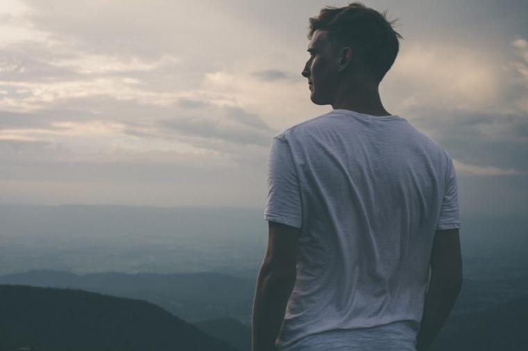 山の上から曇った景色を見る男性