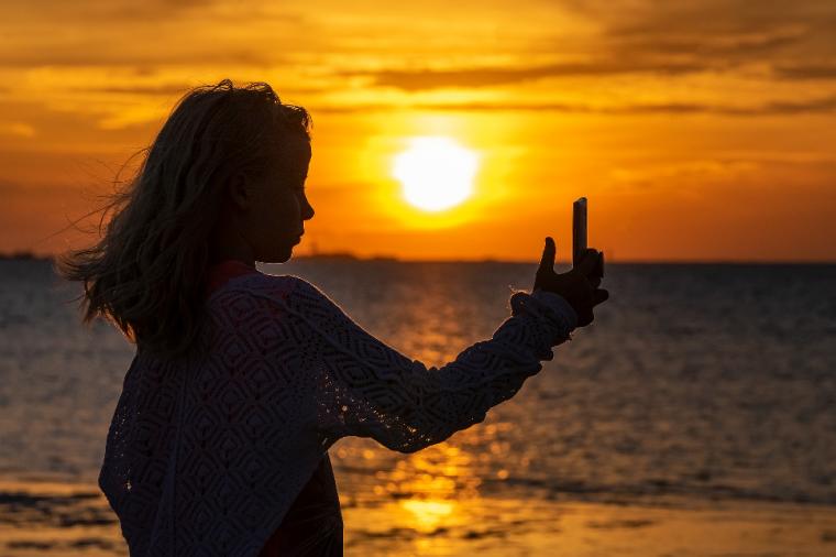 夕焼けを背景に写真を撮る女の子
