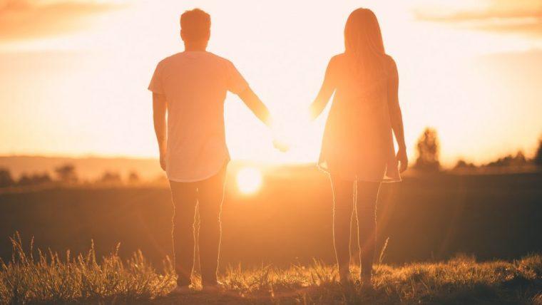 夕日の前で手を繋ぐカップル