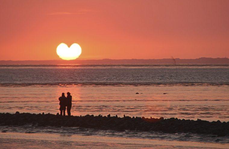 ハート型の夕日とカップル