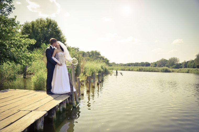 湖のほとりで誓いのキスをする夫婦